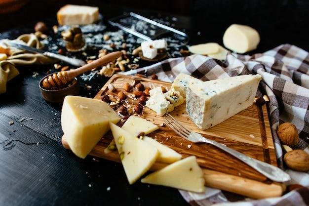 Composition de différentes variétés de fromage avec du miel, des noix, des olives