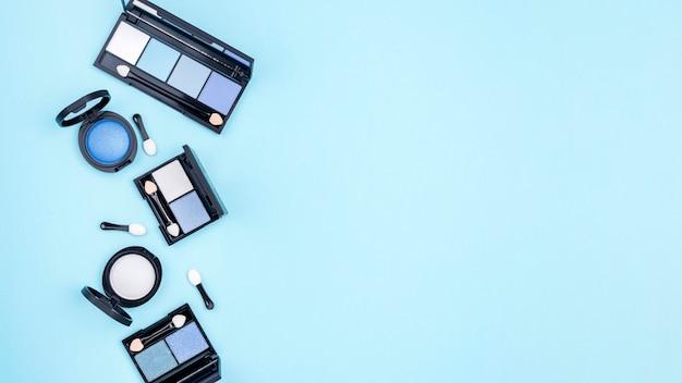Composition de différents cosmétiques avec espace copie sur fond bleu