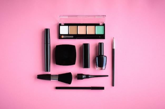 Composition de différents produits de maquillage sur fond rose