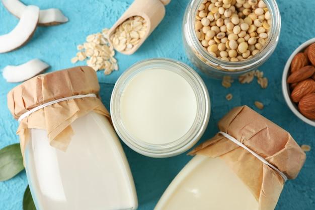 Composition avec différents types de lait, noix de coco, graines de soja, aulne, avoine sur bleu, gros plan. vue de dessus