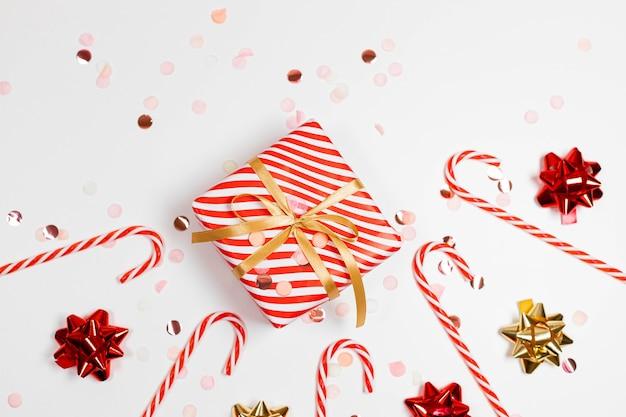Composition du cadre de bonne année 2021. boîtes à cadeaux design rayé de noël, arc doré et rouge, canne à sucre, lumière scintillante sur fond blanc avec espace de copie. mise à plat, vue de dessus