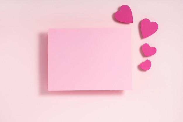 Composition du cadre de la saint-valentin. coeurs violets et roses et feuille de papier vierge sur rose pastel. vue de dessus, mise à plat, fond.