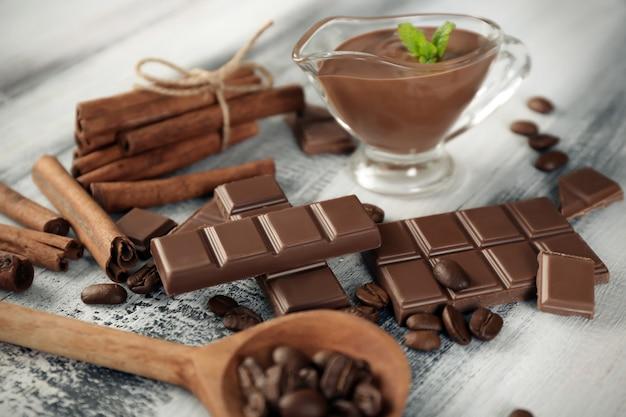 Composition avec du chocolat savoureux, des bâtons de cannelle et des grains de café sur bois