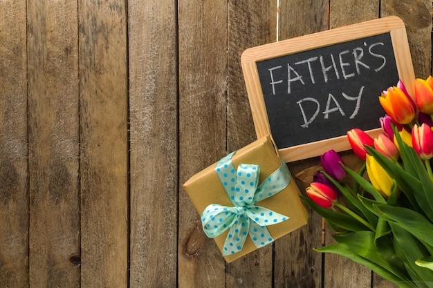 Composition du jour du père avec des fleurs, des cadeaux et de l'ardoise
