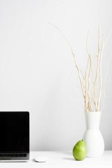 Composition du lieu de travail avec vase et ordinateur portable sur le bureau