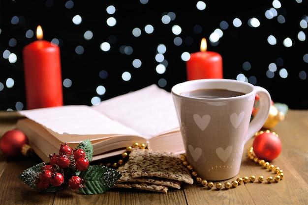 Composition du livre avec une tasse de café et des décorations de noël sur table sur fond sombre