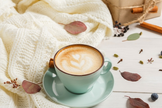 Composition du matin d'automne. tasse à café bleue avec cappuccino mousseux chaud, clous de girofle, cannelle et pull chaud en bois blanc. concept de boissons épicées d'automne