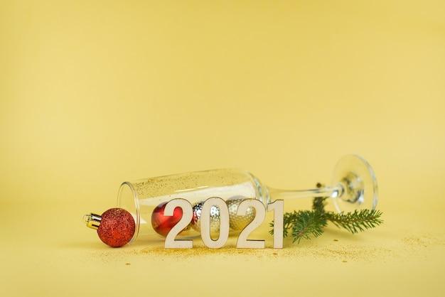 Composition du nouvel an 2021 avec un verre de champagne vide sur fond jaune