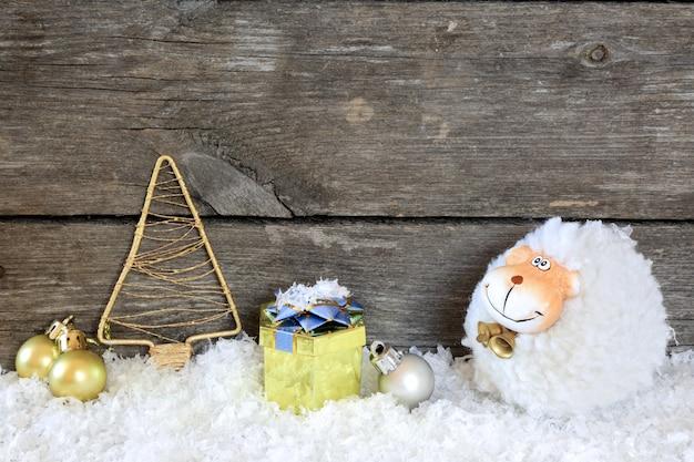 Composition du nouvel an avec un mouton - un symbole de 2015 sur le calendrier oriental, sur un fond en bois gris