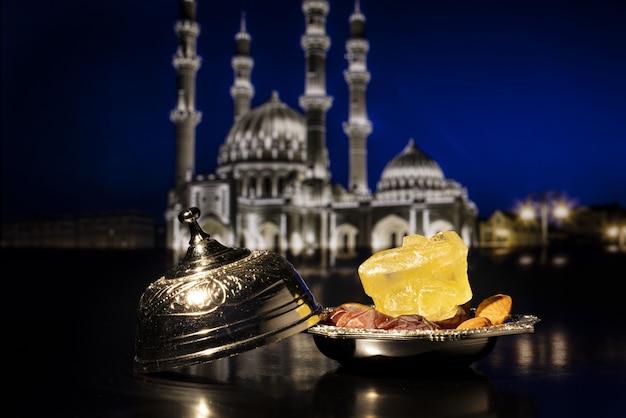 Composition du ramadan avec des dattes séchées sur bol en argent