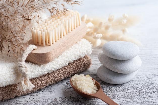 Composition du spa avec du sel et des fleurs sèches sur une table rustique dans un style monochrome. serviette avec bougies et galets blancs. massothérapie aux pierres chaudes pour une personne. traitement de beauté et détente