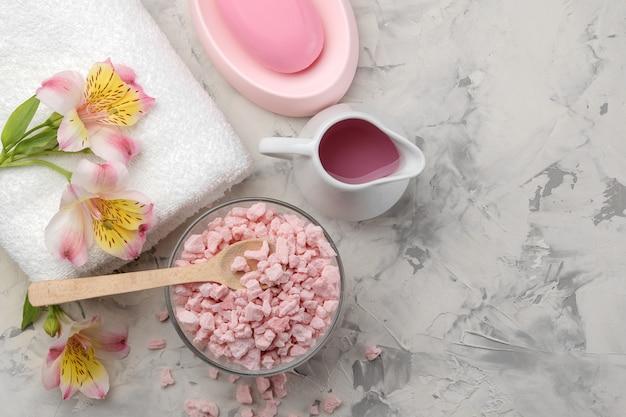 Composition du spa avec du sel de mer, des huiles et une serviette sur du béton gris et blanc