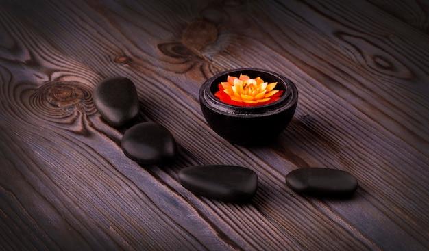 Composition du spa. pierres noires et une bougie sur table en bois