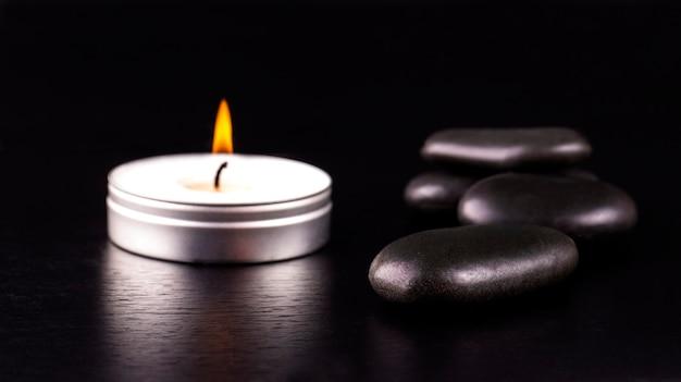 Composition du spa. pierres noires et une bougie sur table noire