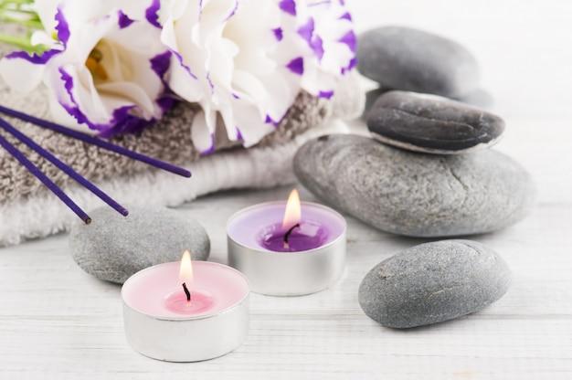 Composition du spa avec des serviettes, des bougies allumées, des bâtons d'arôme violets