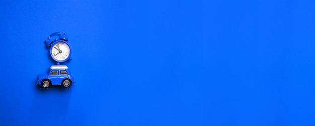 Composition du temps de noël avec petit modèle de voiture pour enfants bleu avec réveil sur le capot sur un bleu