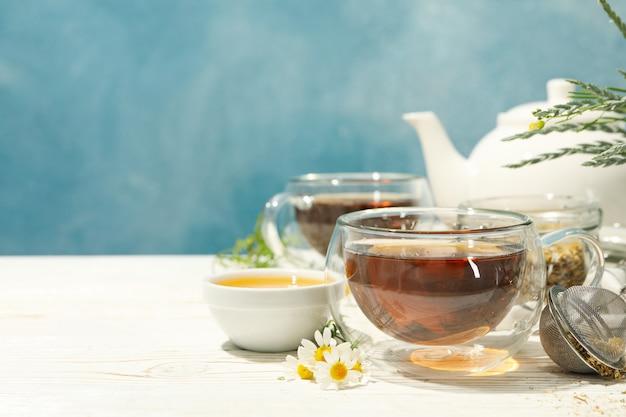Composition avec du thé à la camomille sur une table en bois blanche