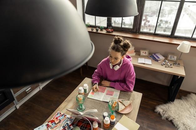 Composition d'écriture. vue de dessus d'une adolescente assise dans la cuisine et écrivant une composition pour l'école