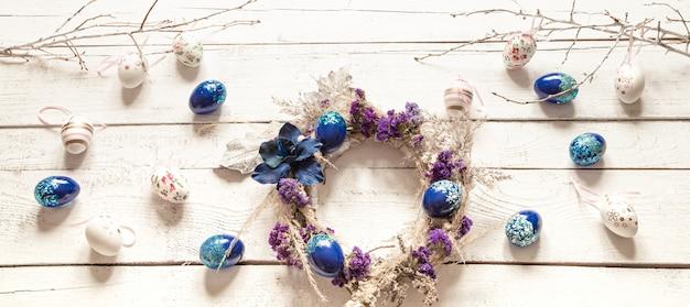 Composition élégante avec une couronne de pâques et des oeufs tendance bleu.