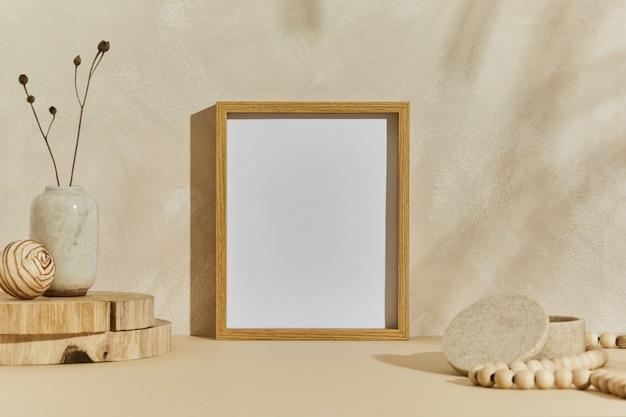 Composition élégante d'un design d'intérieur minimaliste et confortable avec un cadre d'affiche maquette, des matériaux naturels comme le bois et le marbre, des plantes sèches et des accessoires personnels. couleurs beiges neutres, modèle.