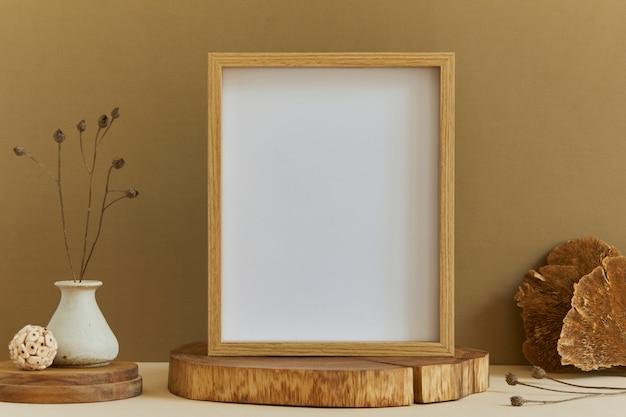 Composition élégante d'un design d'intérieur minimaliste avec une maquette de cadre d'affiche, des matériaux naturels comme le bois et le marbre, des plantes sèches et des accessoires personnels. couleurs neutres et jaunes, modèle.
