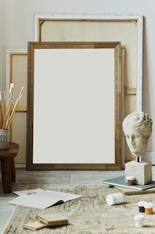 Composition élégante de l'espace de travail de l'artiste avec cadre d'affiche maquette, accessoires de peinture, décor de tapis, décoration et notes. modèle.