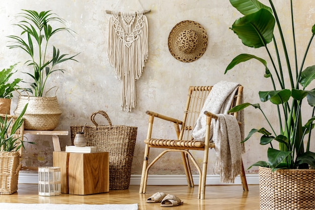 Composition élégante et florale de l'intérieur du salon avec fauteuil en rotin, beaucoup de plantes tropicales dans des pots design.