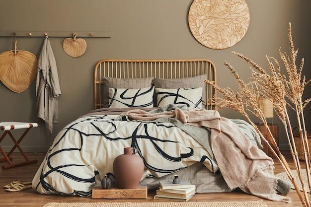 Composition élégante de l'intérieur de la chambre avec lit en bois, meubles, fleurs séchées dans un vase, décoration en rotin, vases et accessoires élégants