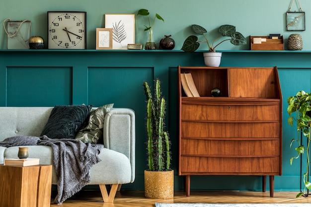 Composition élégante de l'intérieur du salon avec armoire en bois rétro, canapé à la menthe, oreillers, plaid, cactus, plantes, décoration sur l'étagère et accessoires personnels élégants. décor à la maison vintage.
