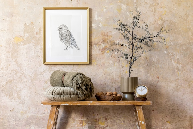 Composition élégante de l'intérieur du salon avec cadre en or, banc en bois, oreiller, plante, noix, horloge, mur grunge et accessoires personnels élégants dans une décoration moderne.