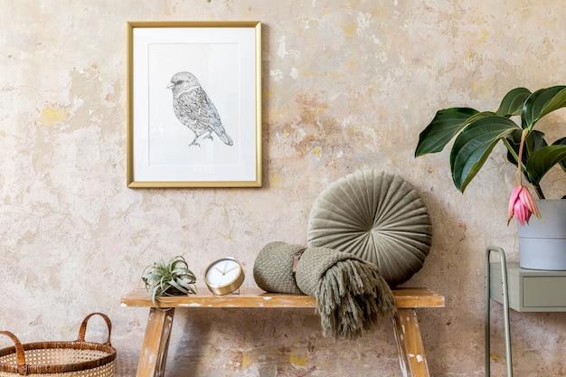 Composition élégante de l'intérieur du salon avec cadre en or, banc en bois, oreiller, plantes, plante aérienne, horloge, mur grunge et accessoires personnels élégants dans un décor moderne.