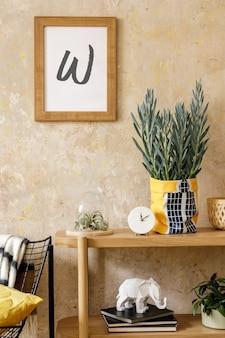 Composition élégante de l'intérieur du salon avec cadre photo, console en bois, fauteuil design, plantes en pot hipster, décoration, livre, mur grunge et accessoires personnels.