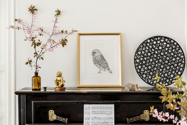 Composition élégante à l'intérieur du salon avec piano noir, cadre d'affiche en or, fleurs séchées, décoration et accessoires personnels élégants dans un décor moderne.
