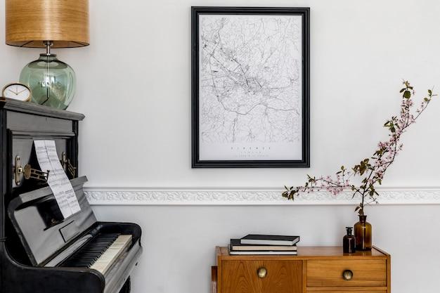 Composition élégante à l'intérieur du salon avec piano noir, commode design, carte d'affiche maquette noire, fleurs printanières, lampe de table et accessoires personnels dans un décor moderne.