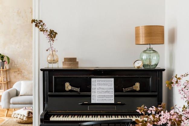 Composition élégante à l'intérieur du salon avec piano noir, fleurs séchées dans un vase, horloge dorée, lampe design, boîtes, espace de copie et accessoires personnels élégants dans un décor moderne.