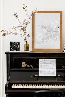 Composition élégante à l'intérieur du salon avec piano noir, maquette d'affiche, fleurs séchées, horloge, livre, lampe, mur blanc et accessoires presonal élégants dans un décor moderne.