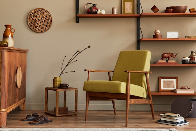 Composition élégante de l'intérieur du salon rétro avec fauteuil design bibliothèque en bois table basse plante tapis pantoufles décoration et accessoires élégants dans la décoration intérieure