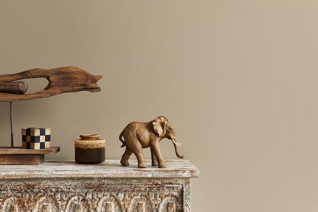 Composition élégante à l'intérieur marocain avec étagère en bois, cube, figure d'éléphant design et décoration dans un décor moderne. détails.. copiez l'espace.