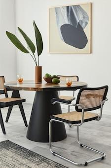 Composition élégante de l'intérieur de la salle à manger avec table design, chaises modernes, décoration, feuille tropicale dans un vase, fruits, maquettes abstraites et accessoires élégants dans la décoration intérieure