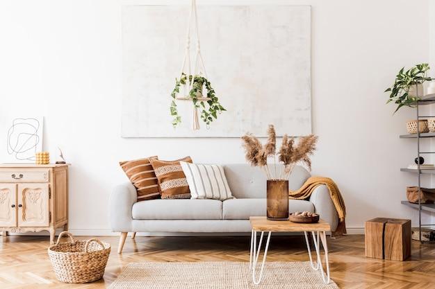 Composition élégante d'un intérieur de salon créatif et confortable avec canapé gris, table basse, plantes, tapis et beaux accessoires. murs blancs et parquet au sol.