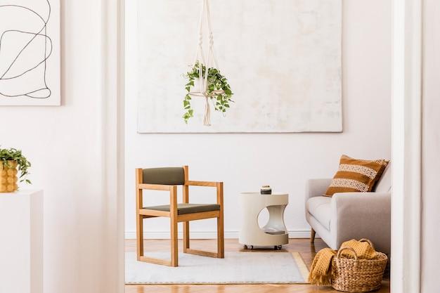 Composition élégante d'un intérieur de salon spacieux et créatif avec chaise, plantes, tapis, peintures et accessoires. murs blancs et parquet au sol.