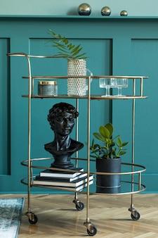 Composition élégante et moderne du salon avec armoire à liqueur design en or, plantes, livres et accessoires personnels élégants. lambris vert avec étagère. décoration d'intérieur moderne..