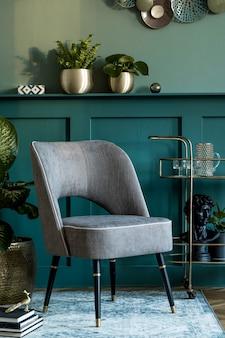 Composition élégante et moderne du salon avec fauteuil design gris, armoire à liqueur dorée, plantes et accessoires personnels élégants. lambris gris avec étagère. décoration d'intérieur moderne..