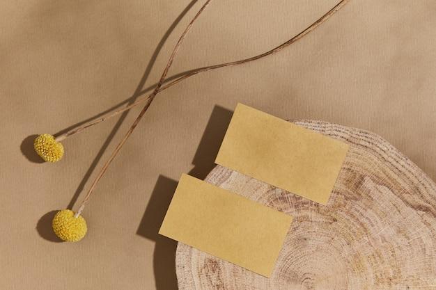 Composition élégante à plat avec maquettes de cartes de visite, bois, matériaux naturels, plantes sèches et accessoires personnels. couleurs neutres, vue de dessus, modèle.