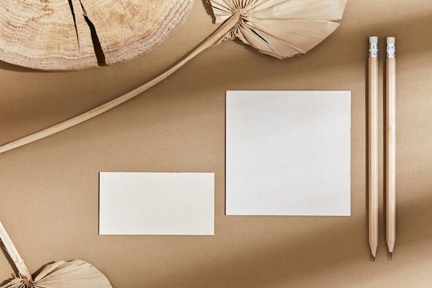 Composition élégante à plat avec maquettes de cartes de visite, textile, roches, bois, matériaux naturels, crayons, plantes sèches et accessoires personnels. couleurs neutres, vue de dessus, modèle.