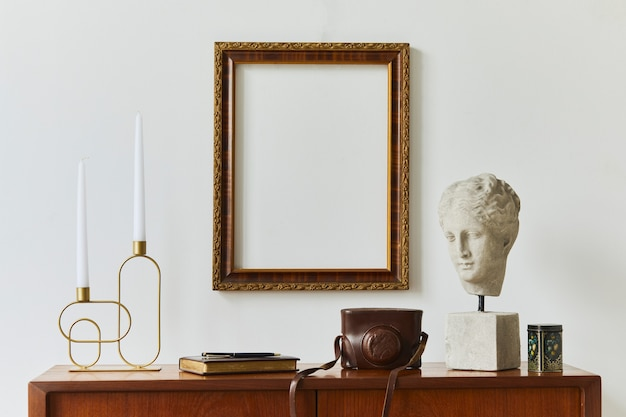 Composition élégante de la salle de travail de l'artiste avec commode rétro en teck design, cadre d'affiche maquette, livre, décoration et accessoires élégants. modèle.