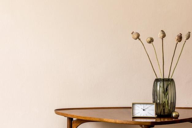 Composition élégante sur la table en bois design avec horloge dorée et fleurs dans un vase.