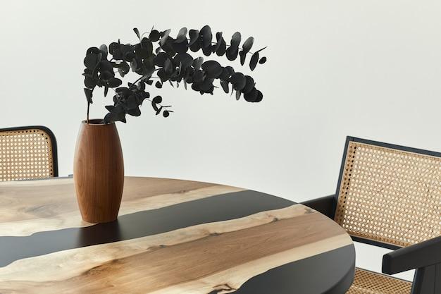 Composition élégante sur la table design avec des fleurs d'eucalyptus noir elegan dans un vase en bois