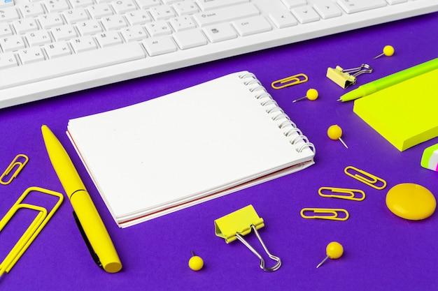 Composition d'éléments de style de vie de bureau sur fond violet, fournitures de bureau clavier d'ordinateur sur le bureau au bureau