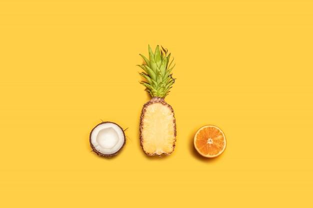 Composition estivale créative de jus de fruits tropicaux sur fond jaune